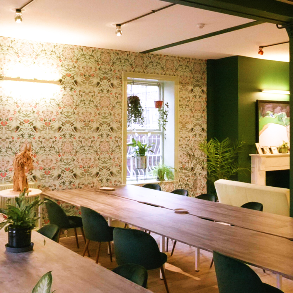 Use.Space co-working space to rent. Tables and chairs in a room with green accents and floral wall paper