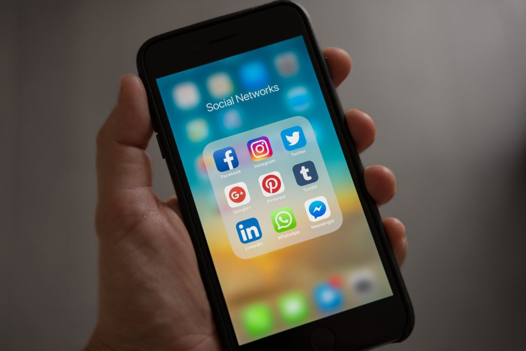 An Apple iPhone showing a social network folder with the following social media applications: Facebook, Instagram, Twitter, Pinterest, tumblr, LinkedIn, Whatsapp and Messenger