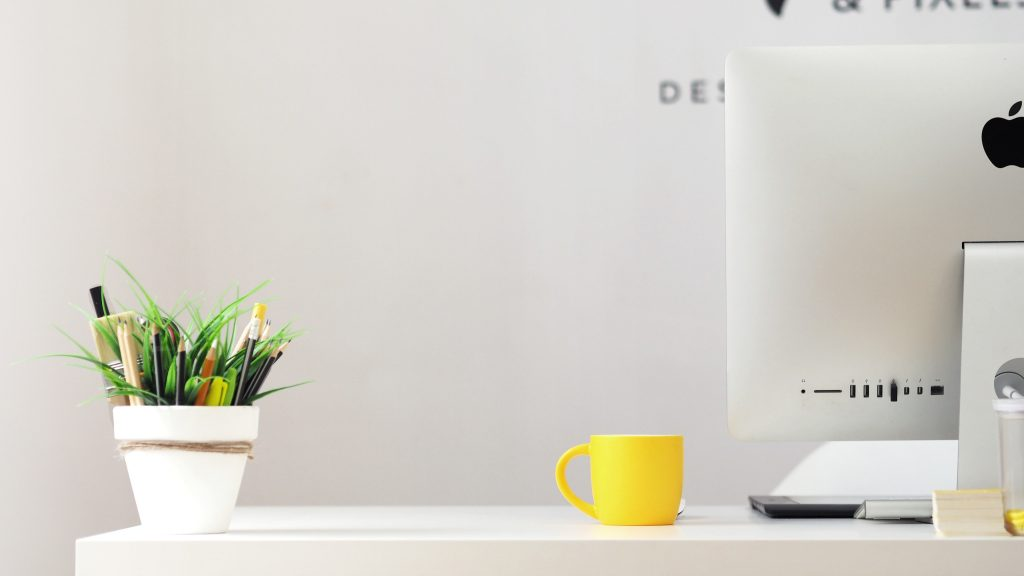 An iMac on a table with a yellow mug and pot plant
