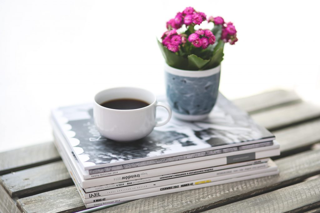 A stack of magazines with a coffee cup and a plant on top
