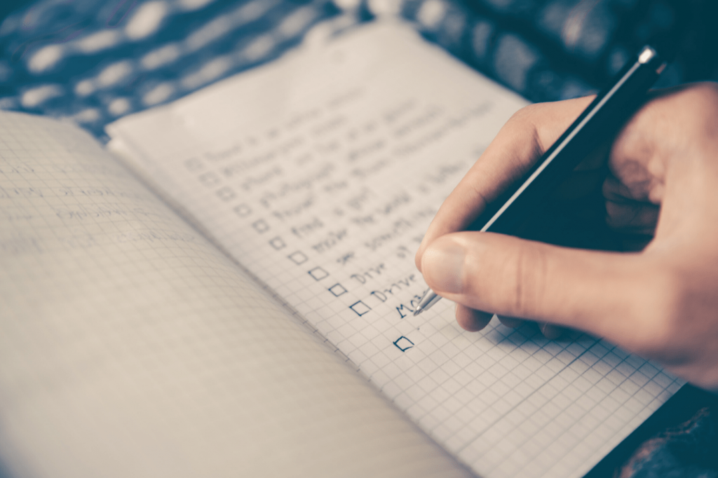 A person writing a list in a notepad